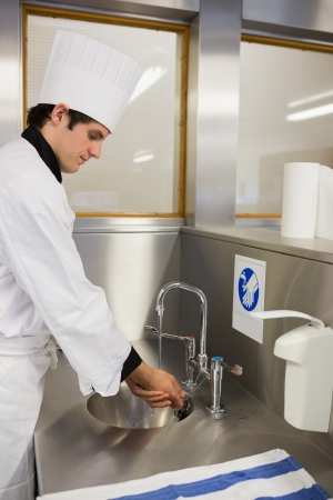 Concentrated chef washing hands in the restaurant photo