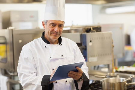 Chef using his digital tablet and looking at camera in the kitchen photo
