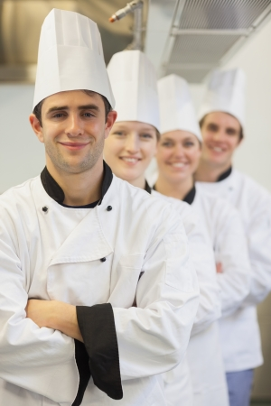 quietness: Smiling chefs assembing in line looking at camera in the kitchen Stock Photo