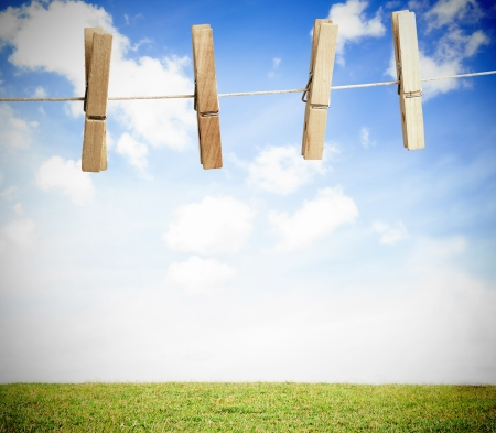 laundry line: Clothespin on a laundry line outside with bright blue sky with green landscape Stock Photo
