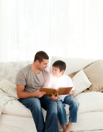 Father and son reading a fairy tale in the living room photo