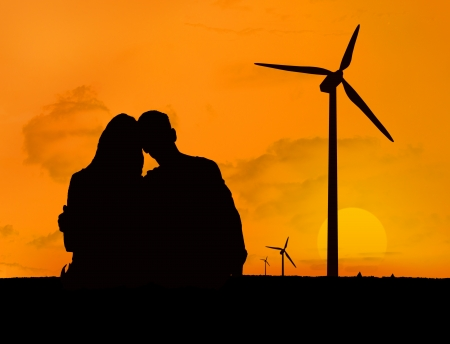 Couple embracing in front of a sunset with silhouettes of wind turbines photo