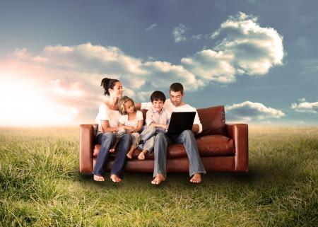 田舎で日当たりの良いフィールドのラップトップを使用してソファで幸せな家族