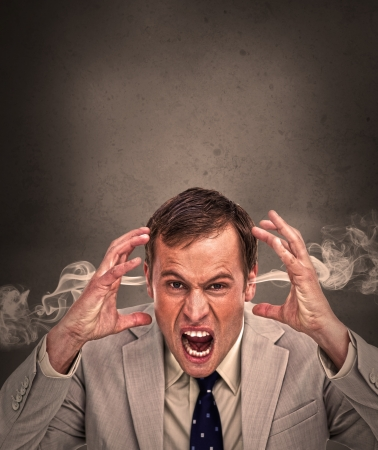 Hot headed business man yelling on brown background with copy space photo