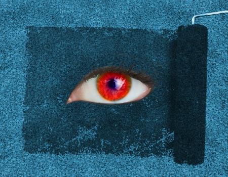 oeil rouge: Rouleau de peinture r�v�lant un ?il rouge sur la texture bleu