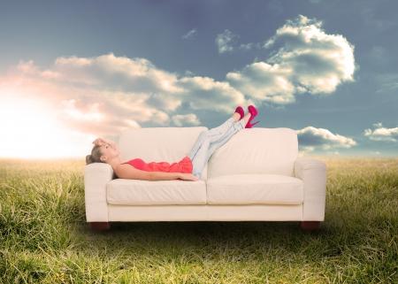 Frau entspannt auf der Couch im sonnigen Feld in der Landschaft