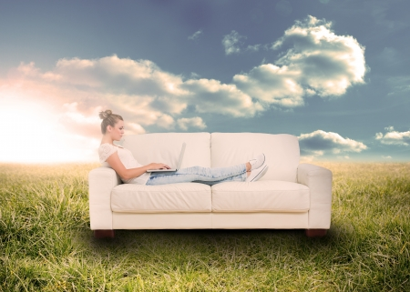 lying on couch: Woman using laptop on couch in sunny field in countryside