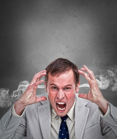 outraged: Hot headed business man shouting on grey background with copy space