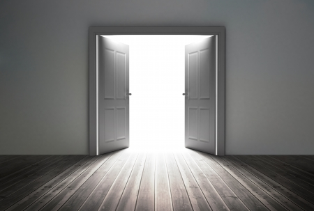 opening door: Doorway revealing bright light in dull grey room Stock Photo