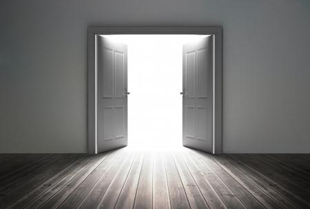 abriendo puerta: Doorway revelando una luz brillante en la habitaci�n gris opaco Foto de archivo