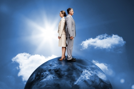 Busines people standing back to back on top of the world in blue sky with sun photo