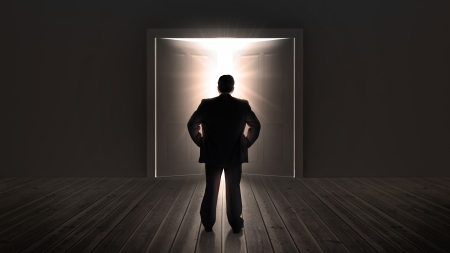 Businessman watching doors opening to a bright light in the shadows photo