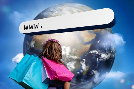 address bar: Girl with shopping bags looking at address bar with large earth in blue sky with clouds Stock Photo