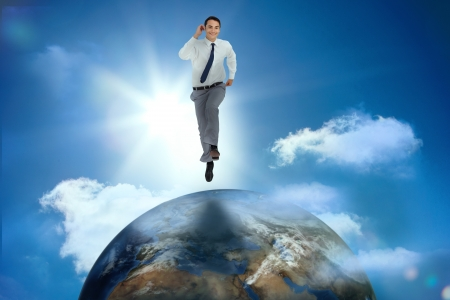 Businessman racing on top of the world in sunny blue sky photo