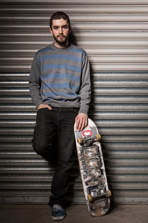 Attractive skater leaning against metal shutters and holding his board in the skate park photo