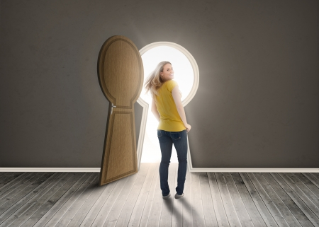 opening door: Woman walking towards keyhole shaped doorway with light ikn dark grey room Stock Photo