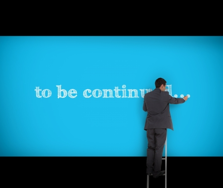 continued: Businessman writing to be continued on a blue wall with a ladder Stock Photo