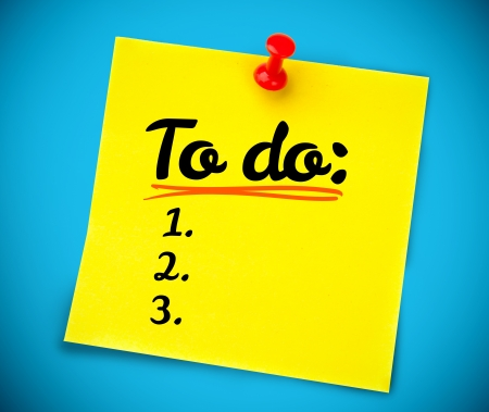 listing: Yellow post it with a to do list written on it on a blue wall Stock Photo