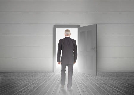 opening door: Businessman walking towards door showing light in a dull grey room