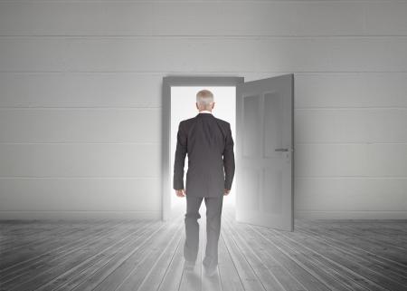 abriendo puerta: Empresario caminando hacia la puerta que muestra la luz en una habitaci�n gris opaco