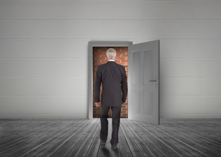 Businessman walking towards door open but blocked by red brick wall in a dull grey room photo