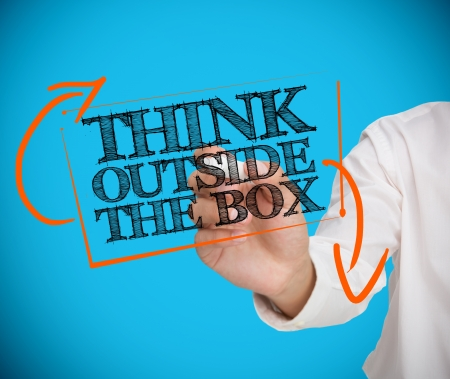 Businessman writing think outside the box with a chalk on blue background photo