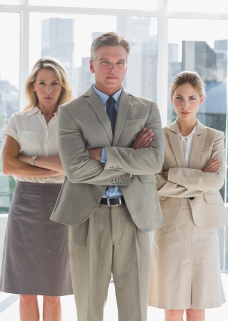 Three serious business people standing together with arms crossed photo