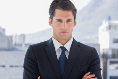 businessman standing: Businessman standing with arms crossed in a bright office