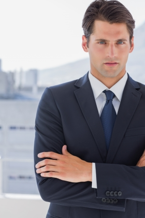 Handsome businessman standing with arms crossed in a bright office photo
