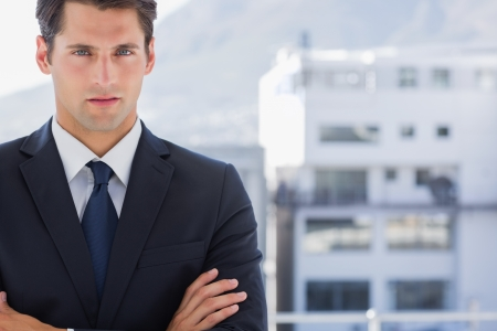 Handsome businessman standing with arms folded in a bright office photo