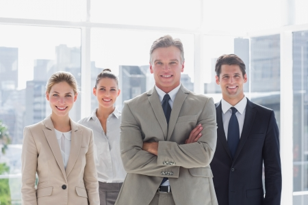 female boss: Boss with his arms folded standing with smiling colleagues behind on a modern office