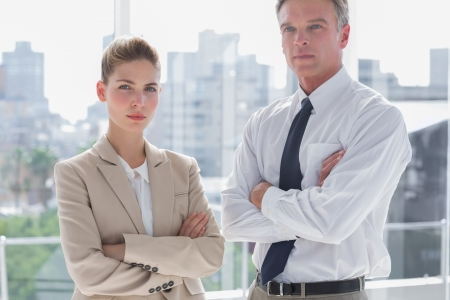 Serious business people with arms crossed in a bright office photo