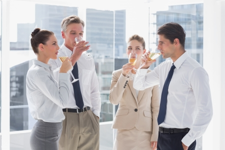 Smiling team of business people drinking champagne in the workplace photo