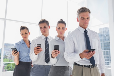 Team of business people standing together in line with their mobile in a modern office photo