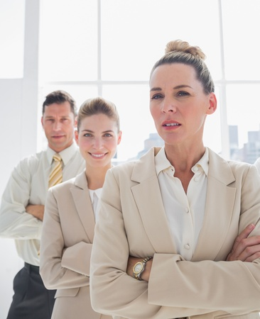 Attractive businesswoman standing with arms crossed in front of colleagues photo