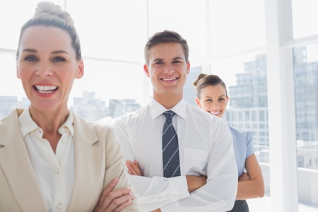 Smiling attractive businesswoman standing with arms crossed in front of colleagues photo