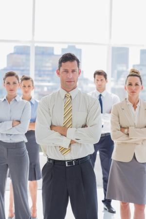 Serious handsome businessman with his team in the office photo