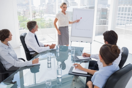 Businesswoman pointing at a growing chart during a meeting photo