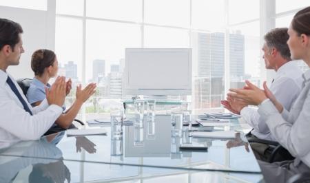 sala de reuniones: Gente de negocios aplaudiendo en una pizarra en blanco durante una reunión