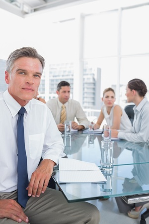 Serious businessman during a meeting with colleagues working behind photo