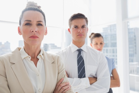 Serious attractive businesswoman standing with arms crossed in front of colleagues photo