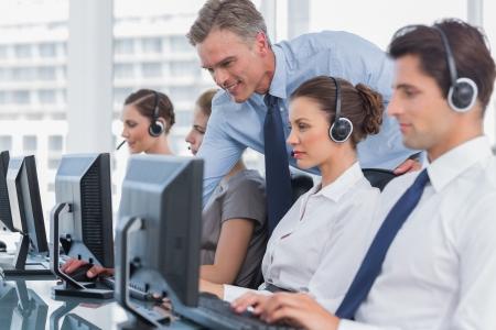 L�chelnder Manager hilft Call Center Agent mit einem Headset