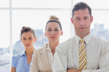 Serious handsome businessman standing with arms folded in their office photo