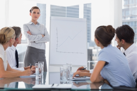 Businesswoman with arms folded in front of a growing chart during a meeting photo