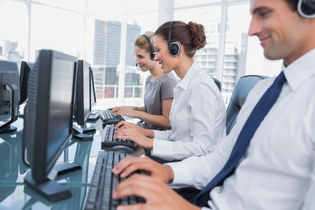 call center office: Group of call center agents working in line in a bright office Stock Photo