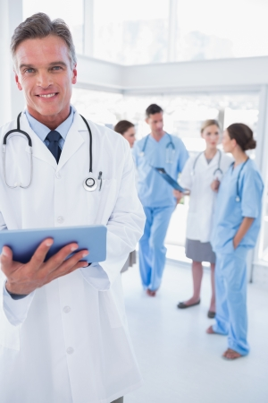 Cheerful doctor holding digital tablet in front of his medical team photo