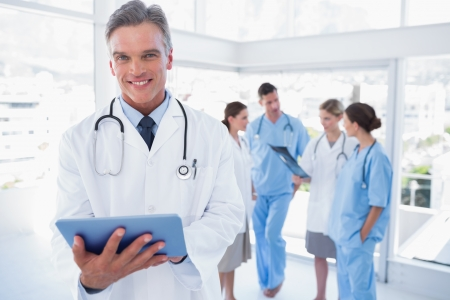 Smiling doctor holding digital tablet in front of his medical team photo