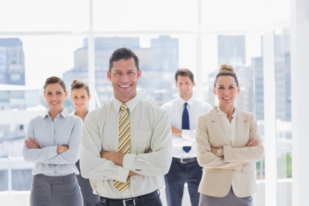 Smiling handsome businessman with his team in a modern office photo