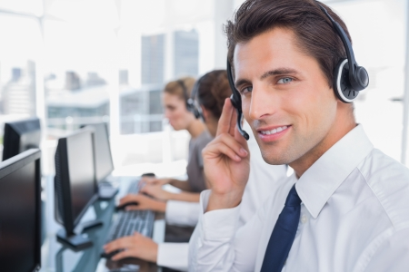call: Portrait of a confident call center agent with his team working behind