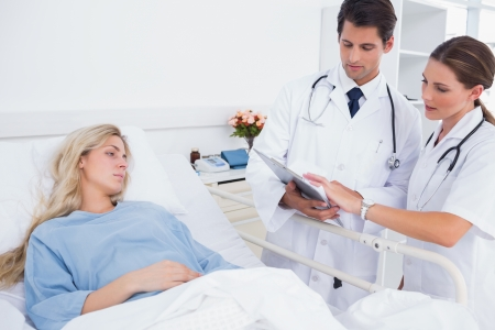 hospitalized: Hospitalized woman and doctors standing next to her Stock Photo